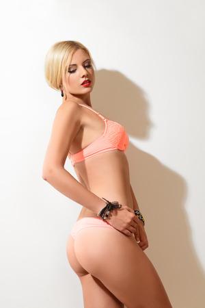 hot breast: Сексуальная молодая стройная женщина в нижнем белье позирует в помещении Фото со стока