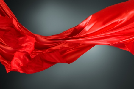 flowing: Abstract silk red cloth motion against dark background