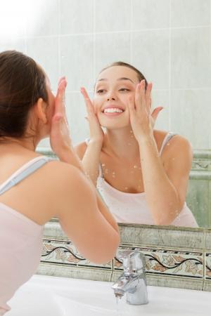 若い女性の浴室できれいな水で顔を洗った