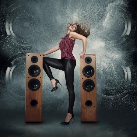 sonido: Concepto abstracto de potentes altavoces de audio explosión fuera una nube de polvo contra el fondo oscuro y una mujer bailando posando delante de ellos