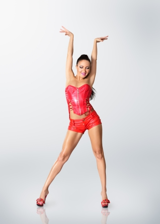 Young woman in stage costume of Go-go dancer posing on studio photo