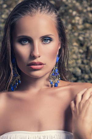 ornated: Young fashion model with blue ornated earrings in front of rock
