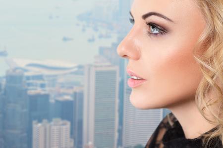 sidewards: Young woman close-up face profile portrait against cityscape view