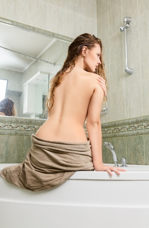 Young woman sitting on side of bathtub  photo