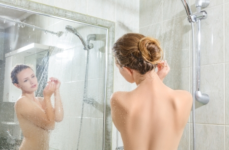 Young woman washing body in a shower. Rear view photo