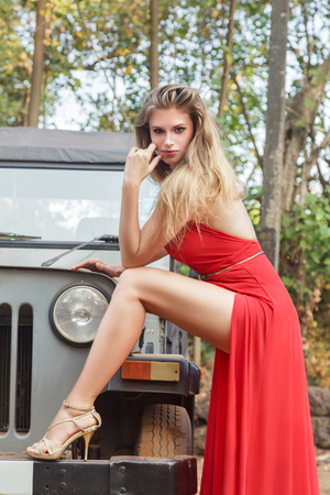 Young woman in a long red dress posing near old military type offroad car photo