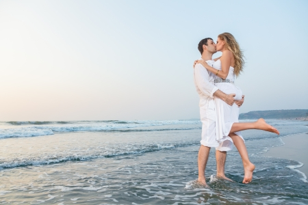 man woman kissing: Young happy couple on a sea beach at sunset
