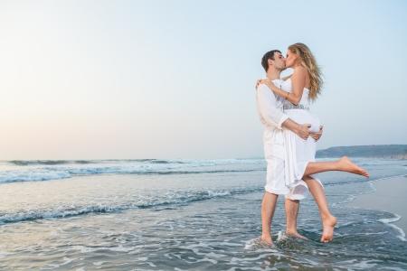 Giovane coppia felice su una spiaggia del mare al tramonto