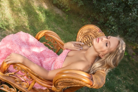 Young woman in luxurious pink dress sitting on chair outdoor portrait photo