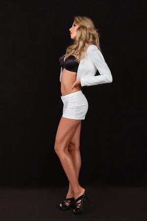 sexy young girls: Молодая женщина в шорты и высокие каблуки обуви позирует на фоне студии Фото со стока