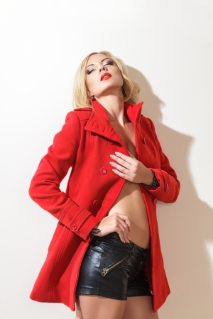 sidewards: Young fashion blonde woman in red coat studio portrait