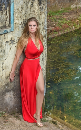 Fashion model in a beautiful long red dress posing near water pool. India, state Goa photo