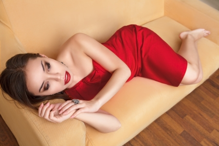 Young beautiful woman in luxurious red dress sitting on a couch photo