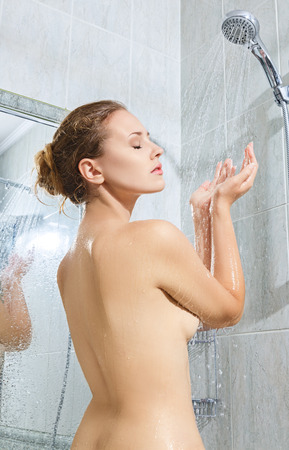 woman in shower: Beautiful young woman taking shower and relaxing