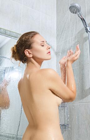 mujer bañandose: Mujer joven hermosa que toma la ducha y relajante Foto de archivo