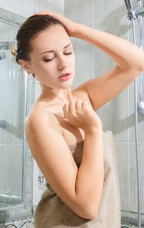 Beautiful young woman taking shower and relaxing photo