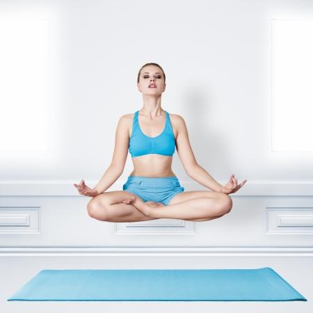 levitacion: Mujer joven en la posici�n asana de loto. La meditaci�n y la levitaci�n concepto Foto de archivo
