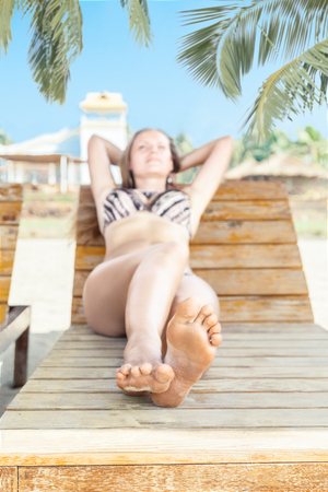 Young woman on beach chair and relaxing in tropical resort photo