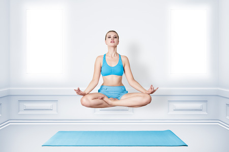 Young woman in lotus asana position. Meditation and levitation concept photo