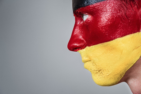 painted lines: Soccer fan with german strip flag painted over face