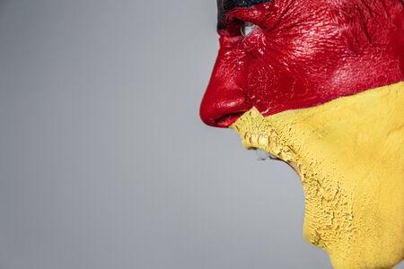 caritas pintadas: Aficionado al fútbol con la bandera alemana pintada tira en la cara Foto de archivo