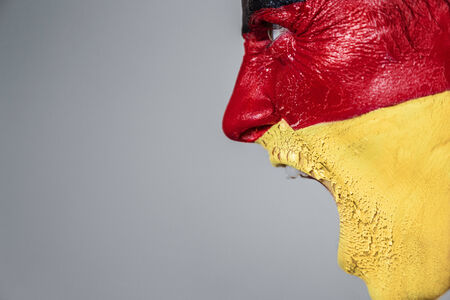 face paint: Soccer fan with german strip flag painted over face
