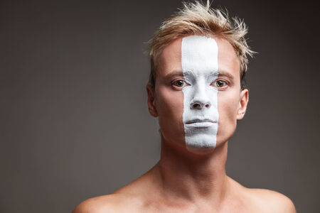 supporter: Soccer fan with white strip flag painted over face Stock Photo