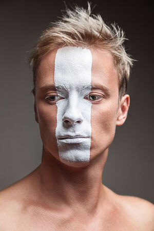 Soccer fan with white strip flag painted over face photo