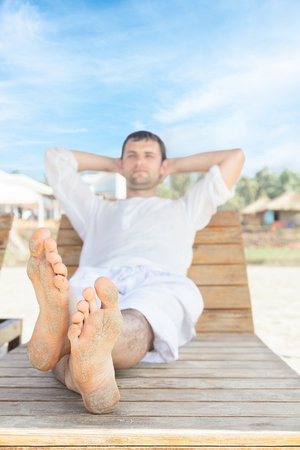 Man lying down on beach chair and relaxing in tropical resort photo