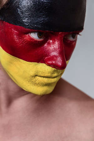 Soccer fan with german strip flag painted over face photo