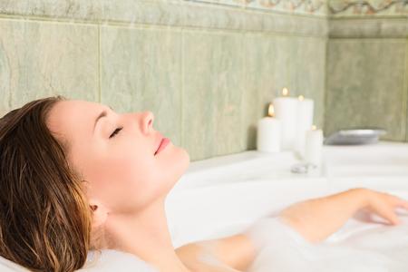 Young beautiful woman relaxing in a bath photo