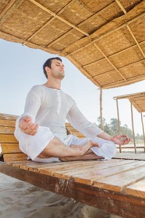 paz interior: Hombre que hace asana de yoga, meditación en posición de loto