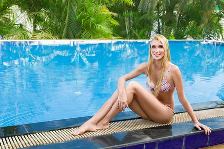 sun bathing: Young woman sun bathing in tropical spa resort swiming pool