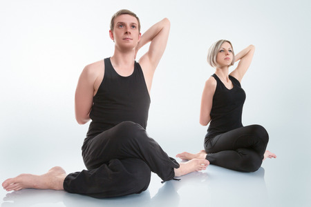 Young man and woman doing yoga in gomukhasana cow face pose photo
