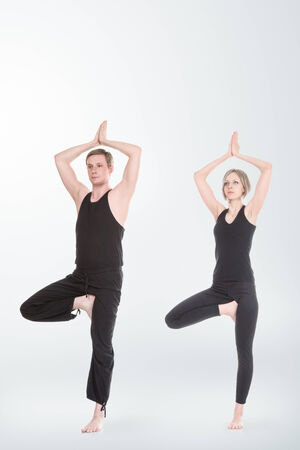 Young man and woman doing yoga and meditating in tree position photo
