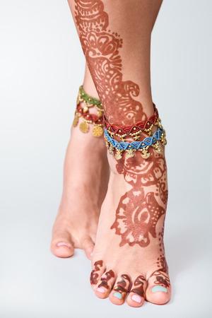 ヘナを描いたインド編成 mehandi で飾られた足および braceletes をクローズ アップ