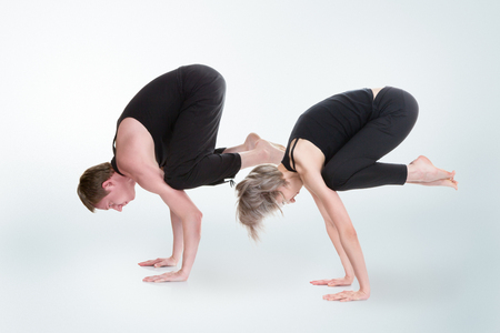 Young man and woman doing yoga and meditating in bakasana crane pose photo