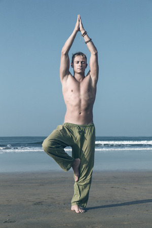 Young man doing yoga and meditating in tree position at sea beach photo