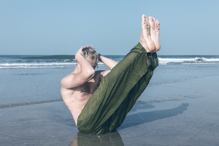Young man doing sit ups during fitness training on sea beach photo