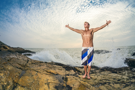swimming shorts: Athletic handsome man in swimming shorts posing in front of tropical sea