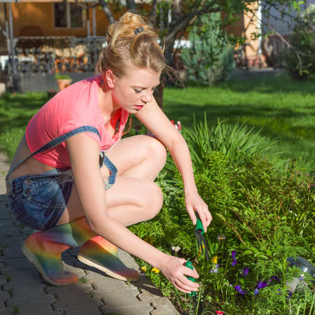 Young blonde woman working in garden sunny day Stock Photo - 26933893