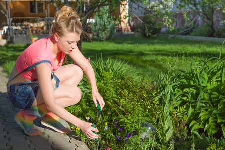 Young blonde woman working in garden sunny day Stock Photo - 27505737