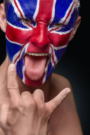 Soccer fan with great britain flag painted over face photo
