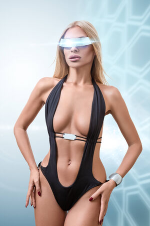 Young fashion futuristic woman posing with virtual reality cyberspace glasses
