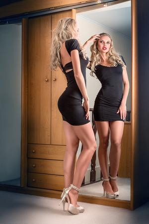 mini dress: Young beautiful blonde woman in black mini dress posing near mirror