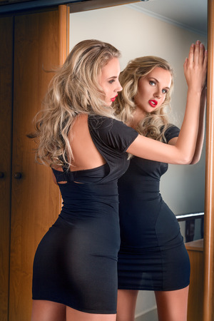 Young beautiful blonde woman in black mini dress posing near mirror photo