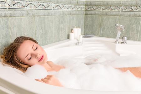 Young beautiful woman relaxing in a bath Standard-Bild