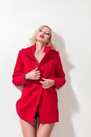 alluring: Beautiful young woman in red coat posing in studio Stock Photo