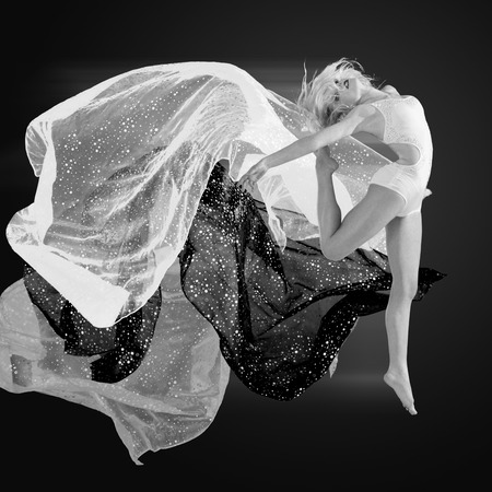 Woman dancing with a strips of fabric over dark background photo