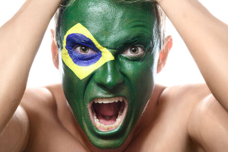 Soccer fan with brazil flag painted over face photo